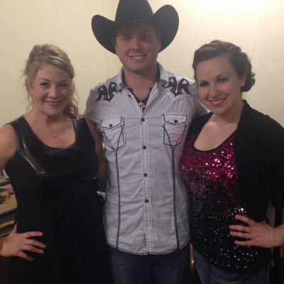 Women pose with a country artist
