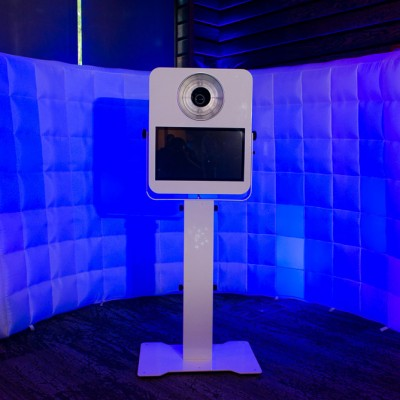A photo booth with an inflatable backdrop and blue lighting