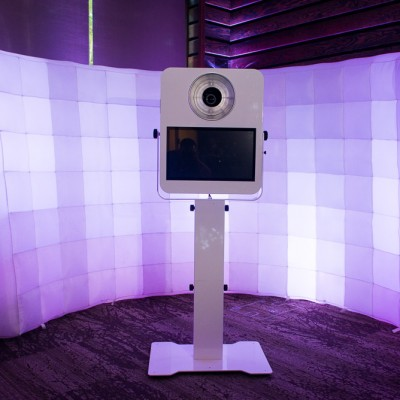 A photo booth with an inflatable backdrop and purple lighting